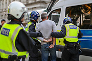 """Police arrest a protestor during a """"Resist and Act for Freedom"""" protest against a mandatory coronavirus vaccine, wearing masks, social distancing and a second lockdown, nearby Canada House in Trafalgar Square, London on Saturday, Sept. 19, 2020. The event, which began at noon, drew a broad coalition including coronavirus sceptics, 5G conspiracy theorists and so-called """"anti-vaxxers"""". Speakers at the event accused the government of attempting to curtail civil liberties. (VXP Photo/ Vudi Xhymshiti)"""