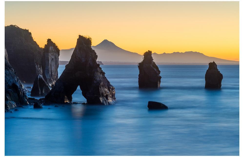 Tongaporutu (The Three Sisters) with Mount Taranaki in the background, Taranaki.