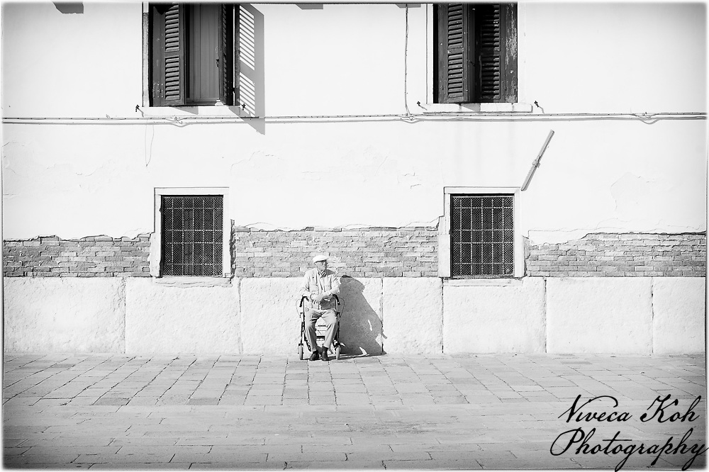 Elderly man sitting on a chair watching the world go by.
