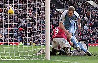 Photo: Paul Thomas.<br /> Manchester United v Manchester City. The Barclays Premiership. 09/12/2006.<br /> <br /> Ben Thatcher of Man City (Blue) can't stop Louis Saha (Red) of Man Utd from scorinf their second for the afternoon.