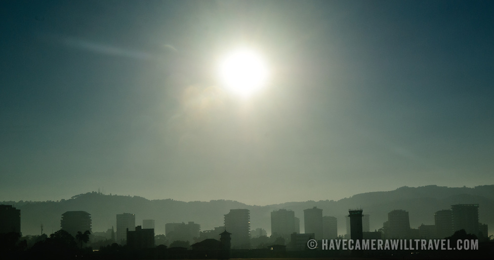 Silhouette of Guatemala City skyline with the mountains in the background against the morning sun taken from Aeropuerto La Aurora (Guatemala City Airport).