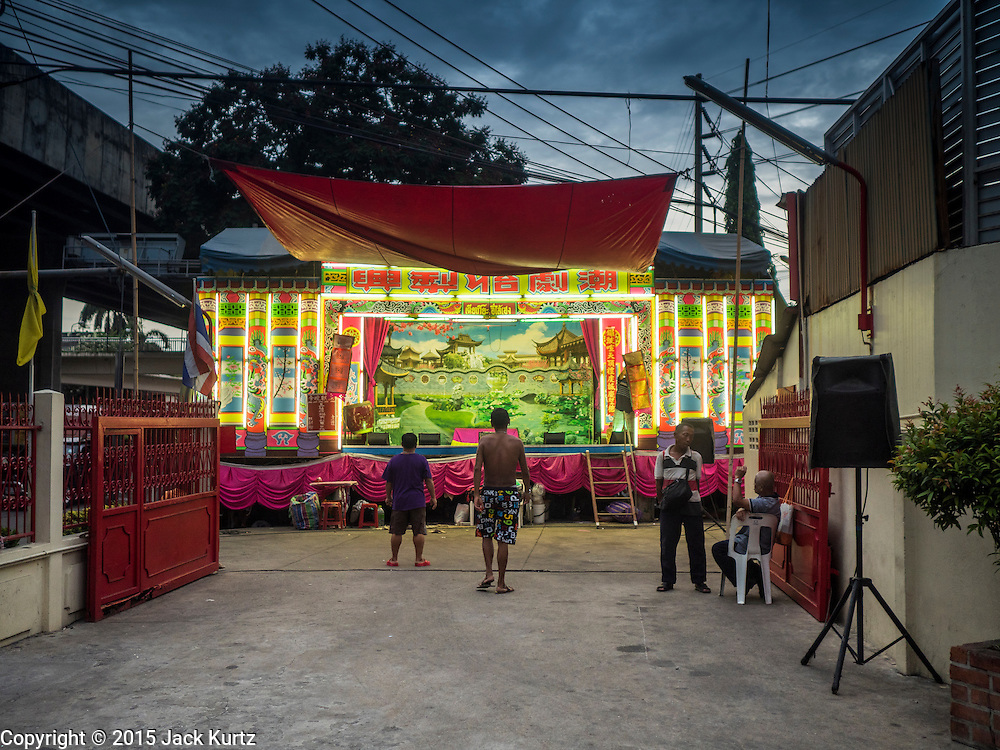 """14 MAY 2015 - BANGKOK, THAILAND:  The stage for a Chinese opera next to Pek Leng Keng Mangkorn Khiew Shrine in the Khlong Toey slum in Bangkok. Chinese opera was once very popular in Thailand, where it is called """"Ngiew."""" It is usually performed in the Teochew language. Millions of Chinese emigrated to Thailand (then Siam) in the 18th and 19th centuries and brought their culture with them. Recently the popularity of ngiew has faded as people turn to performances of opera on DVD or movies. There are still as many 30 Chinese opera troupes left in Bangkok and its environs. They are especially busy during Chinese New Year and Chinese holiday when they travel from Chinese temple to Chinese temple performing on stages they put up in streets near the temple, sometimes sleeping on hammocks they sling under their stage. Most of the Chinese operas from Bangkok travel to Malaysia for Ghost Month, leaving just a few to perform in Bangkok.      PHOTO BY JACK KURTZ"""