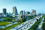 The skyline of downtown Orlando rises above the traffic on Interstate 4, or I-4, a highway that runs east to west through central Florida. The area surrounding the highway is often referred to as the 'I-4 Corridor'.