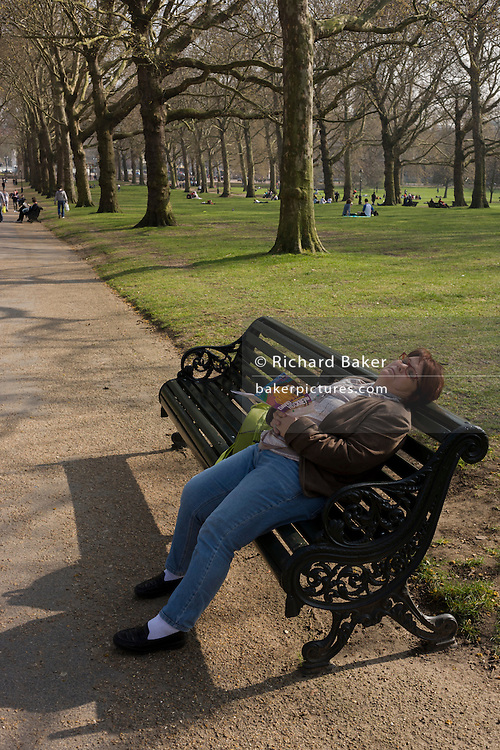 Holding a brochure for the David Hockney art show, a foreign tourist has fallen asleep on a public bench in Green Park.