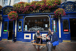 © Licensed to London News Pictures. 16/10/2020. London, UK. Men drinking at a JD Weatherspoon's pub, 'The Toll Gate', in north London. The pub chain announced a £95m annual pre-tax loss, its first since 1984 due to the coronavirus lockdown restrictions on the pub industry. Yesterday, the government announced that from midnight tonight, households in London will not be allowed to mix indoors, including in pubs and restaurants, as London moves into Tier 2 COVID-19 restrictions. Photo credit: Dinendra Haria/LNP
