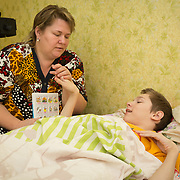 CAPTION: Lybov's son Erik was born with multiple severe disabilities. He has been bed-bound for the past two months, following surgery on his leg. During this time, he has stayed entertained by listening to fairy tales on the Internet, and also from books that his mother reads to him. LOCATION: St Petersburg, Russia. INDIVIDUAL(S) PHOTOGRAPHED: Lybov Chusheva (mother) and Erik Chushev (son).