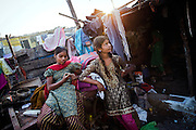 At sunset, while their mother Sangita, 41, (right/back) is tidying up the house,  Poonam, 12, (right) and her older sister Jyoti, 13, are standing in the front yard of their newly built home in Oriya Basti, one of the water-contaminated colonies in Bhopal, central India, near the abandoned Union Carbide (now DOW Chemical) industrial complex, site of the infamous '1984 Gas Disaster'.