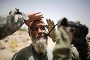 US soldier Spc. Brad Parrish, of Spokane, Wash., from the 1-320th Alpha Battery, 2nd Brigade of the 101st Airborne Division, takes an eye scan of an Afghan villager near COP Nolen, in the volatile Arghandab Valley, Kandahar, Afghanistan, Monday, July 26, 2010. (AP Photo/Rodrigo Abd)
