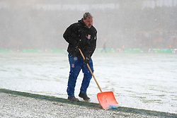 A member of ground staff shovels snow from the pitch during the Premier League match at the bet365 Stadium, Stoke.