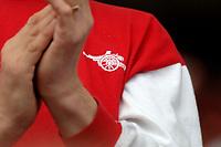 Photo: Daniel Hambury.<br />Arsenal v Wigan Athletic. The Barclays Premiership. 07/05/2006.<br />Arsenal's club badge on a fans shirt.