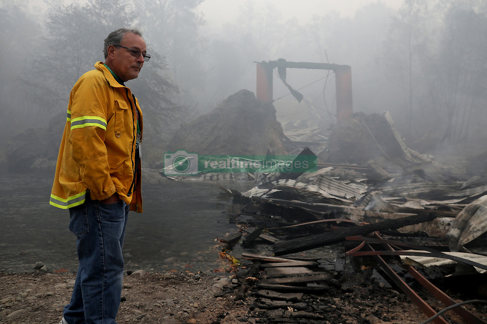 November 10, 2018 - Chico, CA, USA - The iconic 132-year-old Honey Run Bridge sits in ruins on Butte Creek east of Chico, Calif., on Saturday, November 10, 2018. David Little, a fourth generation Chico native and editor of the local Chico Enterprise-Record, surveys the ruins of the famous covered bridge, another victim of the deadly Camp fire. (Credit Image: © Karl Mondon/East Bay Times/TNS via ZUMA Wire)