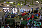 Inmates working as a team to recondition old wheel chairs and bicycles in the Inside Out trust workshop. HMP Liverpool, Merseyside, United Kingdom. Inmates at HMP Liverpool will work during the day in workshops, or doing laundry and other such tasks.