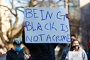 """A protester holds a sign reading """"being black is not a crime."""""""