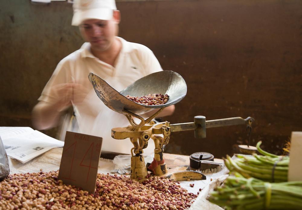 Man weighing beans on old scale, Mercado Agropecuario Cuatros Caminos, Havana, Cuba