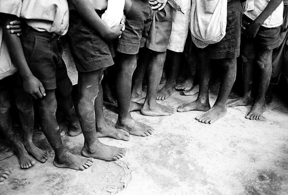 Close up details of boys bare feet in a school, Uganda, East Africa.