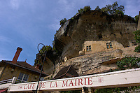 Looking up past the Cafe de la Mairie at part of the National Museum of Prehistory in the village of Les Eyzies-de-Tayac, the Dordgne, region of Aquitaine, Perigord Noir, France.