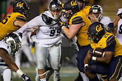 Nevada defensive tackle Dom Peterson (99) pursues California running back Damien Moore (28) through the block of center Matthew Cindric (73) during the second quarter of an NCAA college football game, Saturday, Sept. 4, 2021, in Berkeley, Calif. (AP Photo/D. Ross Cameron)