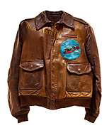 """This type A-2 flight jacket belonged to Darwin E. Arnold, a co-pilot attached to the 568th squadron of the 390th Bomb Group. On the front left of the jacket is the 568th squadron insignia patch, a panther riding on top of a bomb. Above the squadron patch is a name plate that reads """"D.E. Arnold"""". The name """"Hazel Ann"""" is painted on the front right breast of the jacket close to the collar. The back of the jacket contains original artwork, a B-17 flying against the backdrop of a mountain and blue sky with scattered clouds. Below the artwork there are 25 yellow bombs painted on the jacket to signify each successful mission that Arnold flew."""