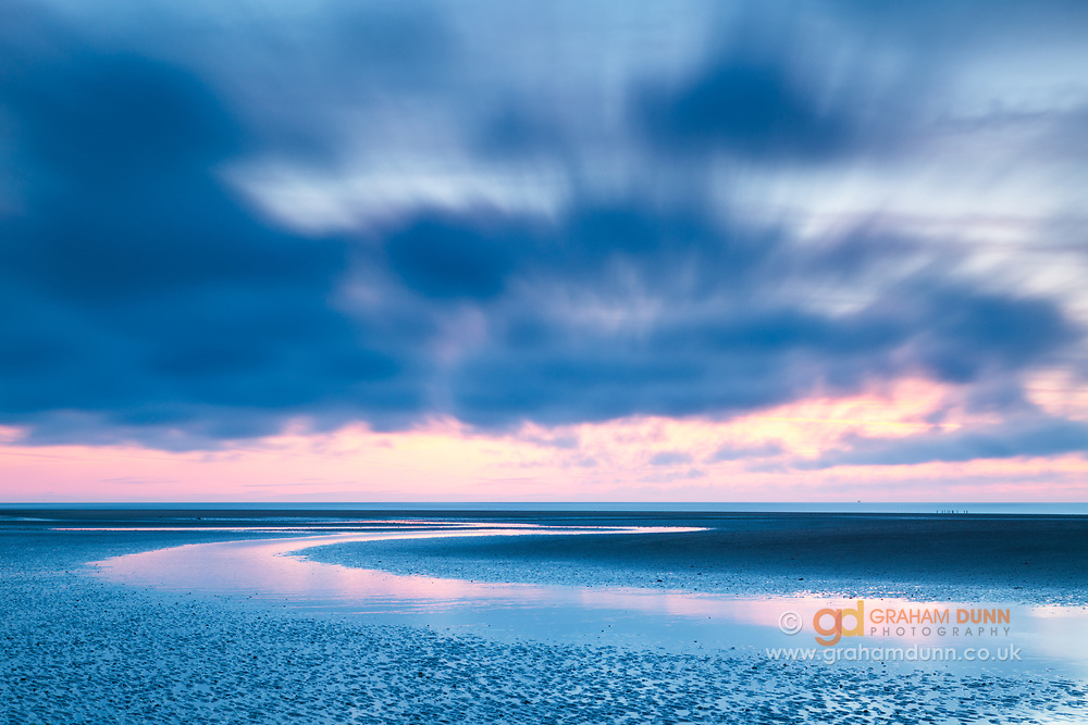 Low level clouds scud across the sky at dusk as a shallow channel reflects the colours in the sky, Old Hunstanton, North Norfolk, East Anglia.