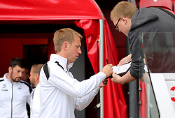Swansea City manager Graham Potter signs an autograph for a fan prior to the beginning of the match
