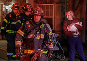 A man holds a cat as members of the Bloomington Fire Department exit a building after a fire at 305 North Pete Ellis Dr., Tuesday, March 19, 2018. The fire was contained to one apartment unit and all three floors of the building were evacuated according to Bloomington Fire Department Battalion Chief Travis Drescher. The cause of the fire is under investigation.