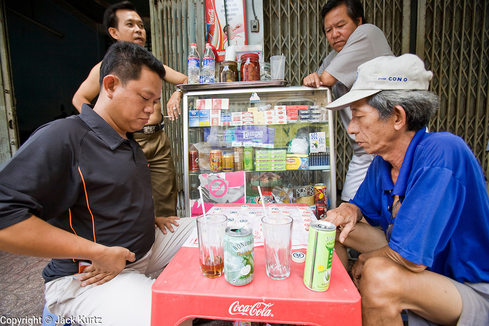 09 MARCH 2006 - HO CHI MINH CITY, VIETNAM: Men play board games in front of a cigarette stand on a sidewalk in Ho Chi Minh City (Saigon), Vietnam.  PHOTO BY JACK KURTZ