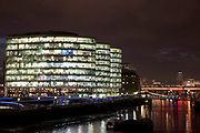 Night scene looking over the River Thames towards More London area offices and business district. This area is a recent development which is now thriving and bustling with more buildings being constructed in this moderm glass style and filling the area with office workers.