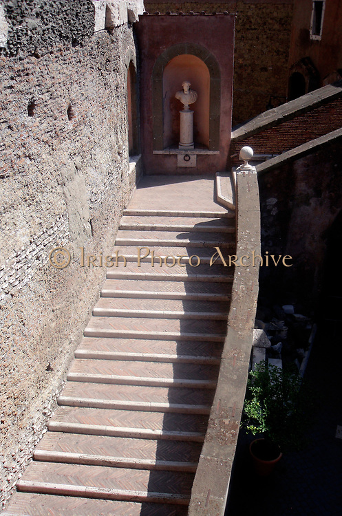 Decorative detail from the area surrounding Castel Sant'Angelo and the Ponte Sant'Angelo in Rome, Italy. Many decorative sculptural and architectural details adorn the length of the bridge, as well as the area surrounding it and the Castel Sant'Angelo. This image shows a bust of the Roman Emperor Hadrian halfway up some stairs.