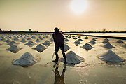 "28 MARCH 2014 - NA KHOK, SAMUT SAKHON, THAILAND: A salt farm manager marks piles of salt in an evaporation pond in Samut Sakhon province. Thai salt farmers south of Bangkok are experiencing a better than usual year this year because of the drought gripping Thailand. Some salt farmers say they could get an extra month of salt collection out of their fields because it has rained so little through the current dry season. Salt is normally collected from late February through May. Fields are flooded with sea water and salt is collected as the water evaporates. Last year, the salt season was shortened by more than a month because of unseasonable rains. The Thai government has warned farmers and consumers that 2014 may be a record dry year because an expected ""El Nino"" weather pattern will block rain in mainland Southeast Asia. Salt has traditionally been harvested in tidal basins along the coast southwest of Bangkok but industrial development in the area has reduced the amount of land available for commercial salt production and now salt is mainly harvested in a small parts of Samut Songkhram and Samut Sakhon provinces.    PHOTO BY JACK KURTZ"
