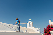 Greece, Amorgos, the Chora. man painting the roof of the church
