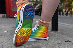 © Licensed to London News Pictures. 07/07/2017. London, UK. A man wears rainbow coloured tennis shoes as rainbow flags and banners, a symbol for the LGBT community, are on display as Soho prepares for the annual Pride parade tomorrow.   Photo credit : Stephen Chung/LNP