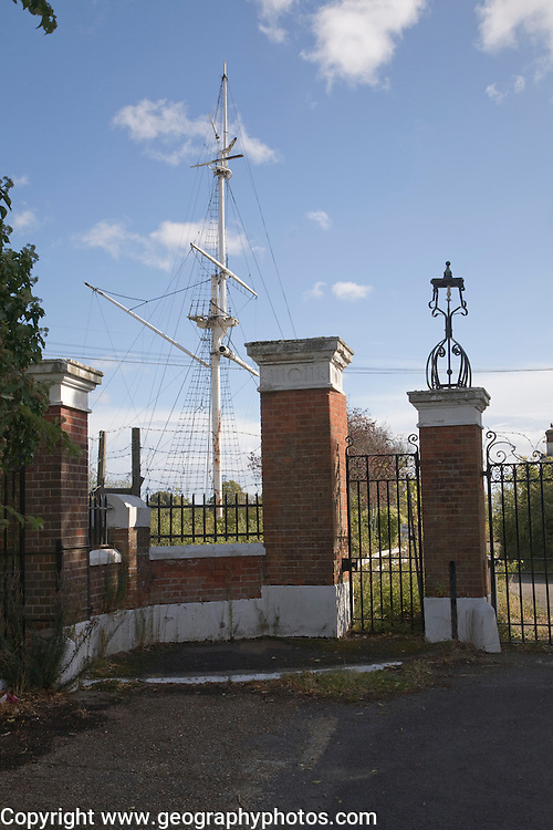 Overgrown buildings, entrance and mast of abandoned HMS Ganges Royal Navy training college, Shotley, Suffolk, England