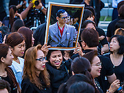 05 DECEMBER 2016 - BANGKOK, THAILAND:  A woman carries a portrait of the late King to a ceremony honoring His Majesty on Bhumibol Bridge. Tens of thousands of Thais gathered on Bhumibol Bridge in Bangkok Monday to mourn the death of Bhumibol Adulyadej, the Late King of Thailand. The King died on Oct 13 after a lengthy hospitalization. December 5 is his birthday and a national holiday in Thailand. The bridge is named after the late King, who authorized its construction. 990 Buddhist monks participated in a special merit making ceremony on the bridge.      PHOTO BY JACK KURTZ