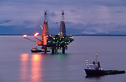 Alaska. Cook Inlet. Dolly Varden off shore oil and gas production platform at night with work boats.