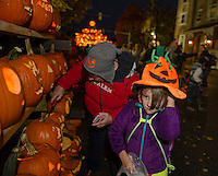Lucy LeBlanc and Delaney Dowling help light the pumpkins lining Main Street during Saturday's Pumpkin Fest.  (Karen Bobotas/for the Laconia Daily Sun)
