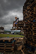 Young boy sits at the base of a huge bonfire in Larne, waiting for the midnight festivities to begin. Belfast, NI, 2021.
