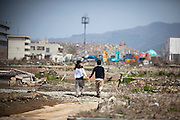 A couple walks around destroyed town, taking their hands each other in Ishinomaki city.