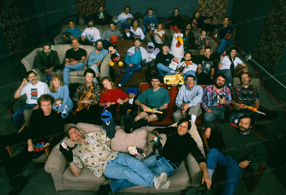 Pixarians lounge with CEO Jobs on couch front right and John Lasseter lying down on couch, in screening room before the launch of movie Toy Story.  All the animators in the picture became multi-millionaires their stock options.