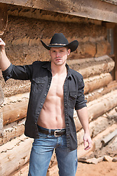 cowboy with an open shirt by a cabin