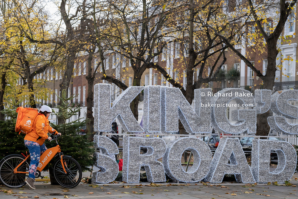 A Just Eat delivery rider pedals past Christmas themed lettering on the King's Road in Chelsea during the second Coronavirus lockdow when - apart from takeaways - most non-essential retailers and small businesses remain closed by order of the government, on 13th November 2020, in London, England.