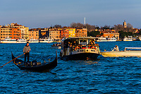 A gondola and vaporetto (water bus) in the Venice Lagoon, Venice, Italy.