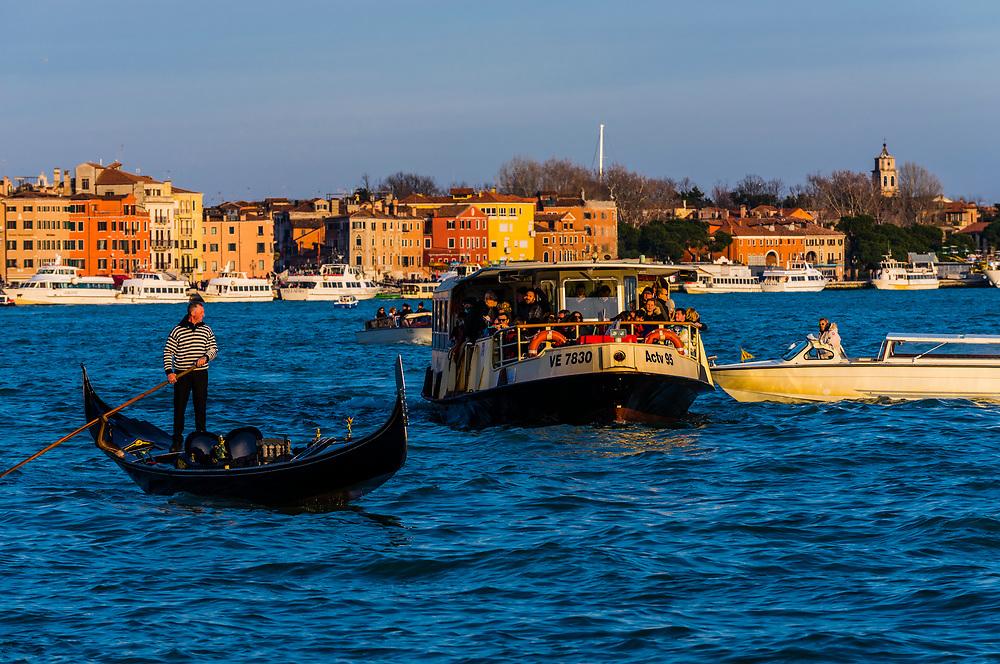 A gondola and vaporetto (water bus) in the Venice Lagoon, Venice, Italy.