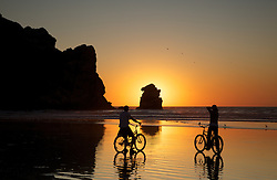 Bicyclers silhouette by the setting sun admire sunset on the Beach at Morro Bay  California.