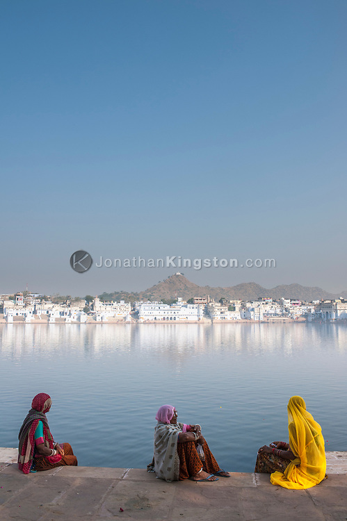 Three elderly sari clad women sitting at the edge of Pushkar lake.