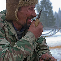 North of the Arctic Circle in Russia, a nomadic Komi reindeer herder eats grilled reindeer meat as he waits for animals to arrive to pull his sled.