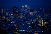 A view of the city of London at night from the top of the BT tower. The square mile and Canary Wharf can be seen.