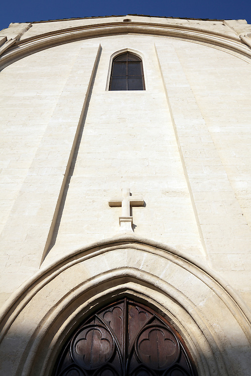 upwards view of the exterior of a church with cross above the door