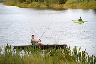 Fishermen use kayaks while fishing on a lake in the Hunter's Creek neighborhood in Orlando, Fla., Wednesday, Aug. 24, 2016. (Phelan M. Ebenhack via AP)