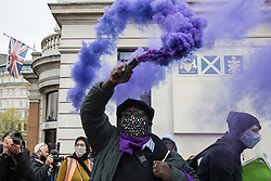 London, UK. 1st May, 2021. A man holds a purple smoke grenade in Trafalgar Square at a Kill The Bill demonstration as part of a National Day of Action on International Workers Day. Nationwide protests have been organised against the Police, Crime, Sentencing and Courts Bill, which would grant the police a range of new discretionary powers to shut down protests.
