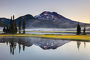 South Sister is reflected on the water of Sparks Lake on a foggy summer morning in Deschutes County, Oregon. South Sister, at 10,363 feet (3,159 meters) tall, is the tallest and youngest volcano in Oregon's Three Sisters group, last erupting about 2,000 years ago. Yellow spear-leaf arnica (Arnica longifolia) flowers bloom on a small island in Sparks Lake.